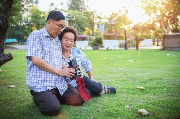 Жизнерадостные азиатские старшие пары наслаждаясь с фотографией в парке с ретро камерой