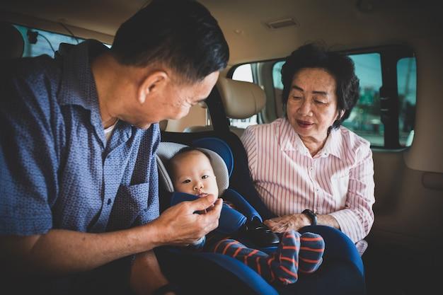 祖母と祖父は車の中で彼女の小さな孫娘の世話をし、彼女を助け、元気づけます