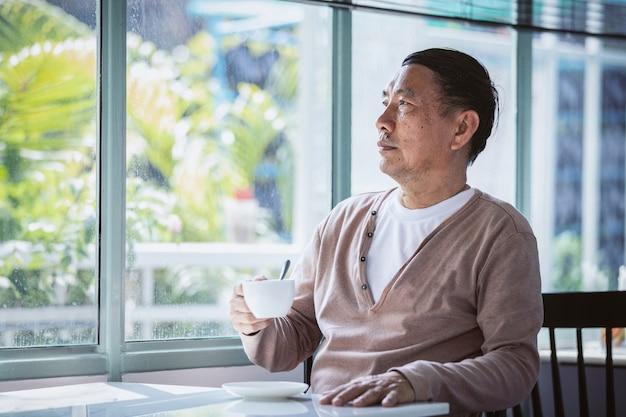 アジアのシニア男性の肖像画は、コーヒーのマグカップを探していると思考の概念を保持します。