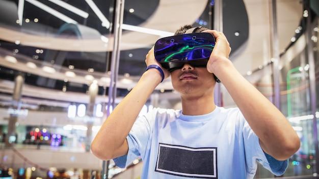仮想現実を身に着けている男の子はゴーグルします。