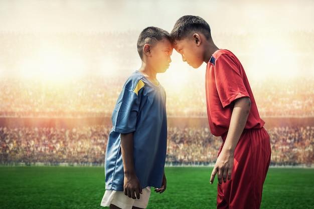 スタジアムでのアクションでのライバルサッカーの子供たち