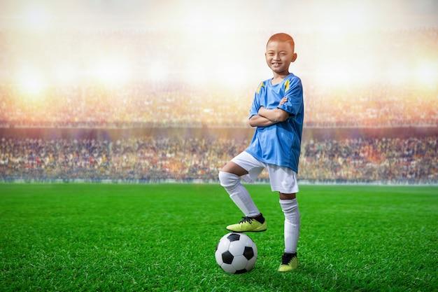 アジアのサッカーの子供たちがスタジアムでサッカーボールの上を歩く