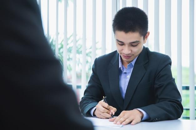 ビジネスマンは、求職活動、面接のコンセプトを確認するために雇用主に履歴書を提出する