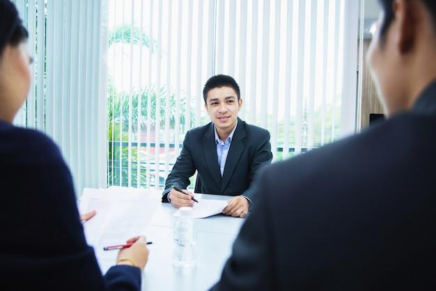 アジア系のビジネスマンが会議で文書やアイデアを議論します。