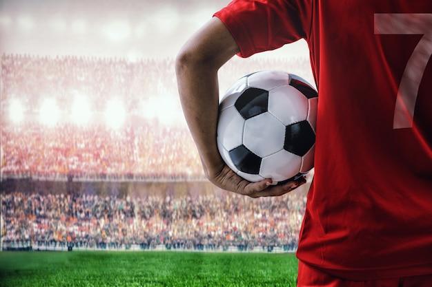 Красный футболист команды на стадионе