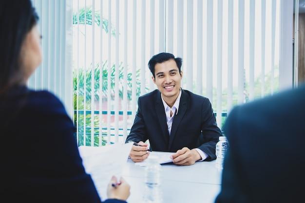 アジア系のビジネスマンの候補者は就職の面接で彼のプロフィールアプリケーションを提示します。