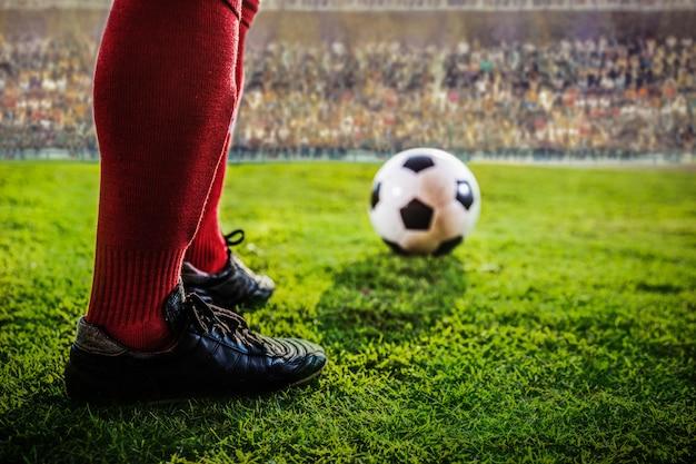 スタジアムでサッカーの真っ赤な足