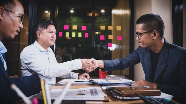 Азиатские бизнесмены обсуждают работу, сидя в конференц-зале офиса на ночной сцене