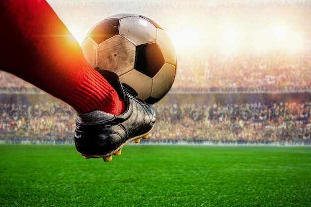 スタジアムでボールを蹴る赤いサッカー選手