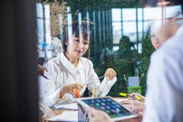 Азиатские деловые люди работают вместе над проектом и мозговой штурм в офисе ночью
