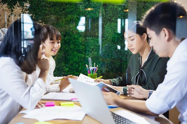 プロジェクトに一緒に取り組んで、夜オフィスでブレーンストーミングアジアのビジネス人々