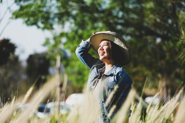 芝生のフィールドで幸せなアジアの女性