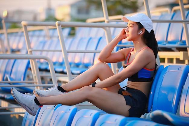 スタジアムシートでのトレーニングの後音楽でリラックスしたアジアの女性