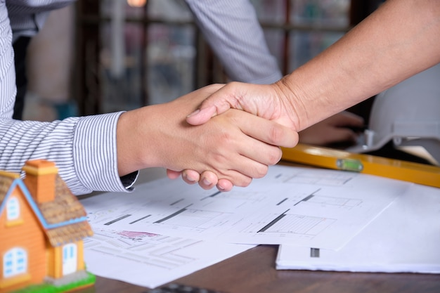 建築家と建設労働者または請負業者は、契約を終えた後、テーブルの設計図と握手しています。