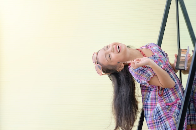 Азиатка маленькой девочки счастлива с косметикой перед зеркалом