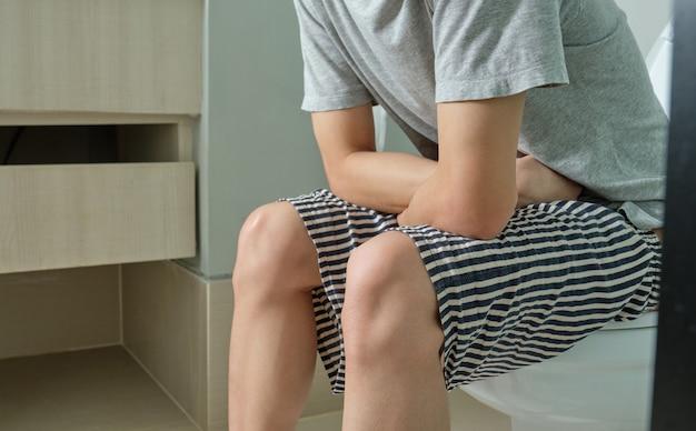 Молодой человек используя руку для того чтобы уловить его живот пока сидящ в туалете для табуретки.