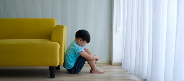 自宅の黄色のソファの横に座っている小さな男の子。子供の自閉症。