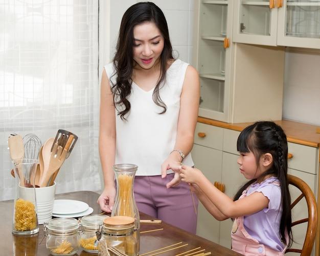 若い母親は、台所で娘のために料理をする方法を教えています。