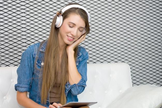 かなり若い女性はソファに座って、タブレットから音楽を聴くためのヘッドフォンを着ています。