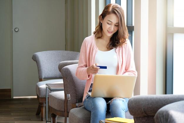 Молодая женщина держа кредитную карточку для ходить по магазинам онлайн пока использующ компьтер-книжки в усмехаясь настроении.
