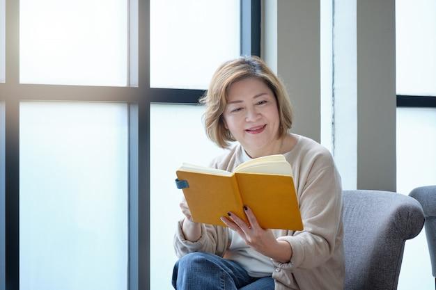 コーヒーを飲みながらリラックスした日に窓辺で本を読んでいる高齢者の女性。