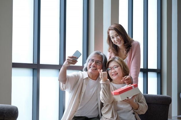 Счастливая семья дарит друг другу подарки в важных случаях и фотографируется.