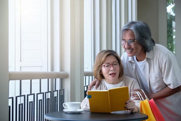 年配のカップルは買い物に行き、本を読んで、休暇、幸せな家族の概念にコーヒーを飲みます。