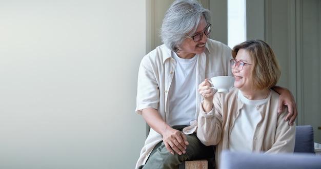 Счастливая семья, пожилые супружеские пары, обнимая и дразня в то время как пить кофе.