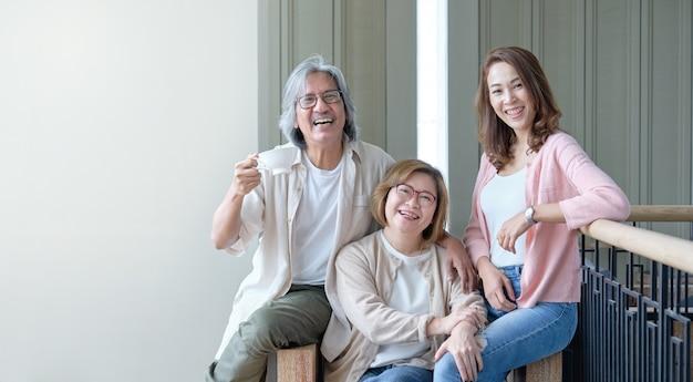 両親と娘は、家族の中で一緒に写真を撮りながら、リビングルームでお互いを喜んで受け入れます。