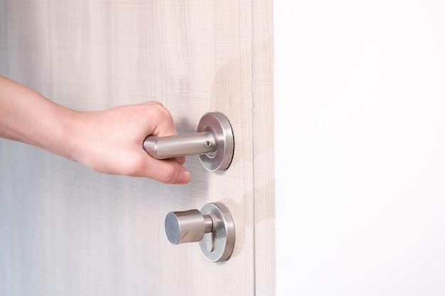 ドアの取っ手を持っている男性の手。