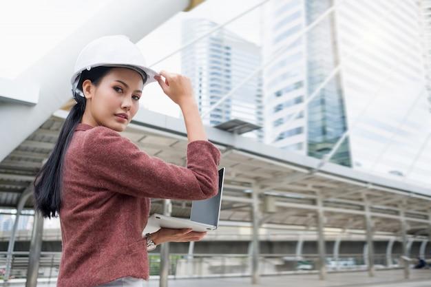 自信を持ってアジアの働く女性はヘルメットを着用し、屋外に立っている間、ラップトップに取り組んでいます。