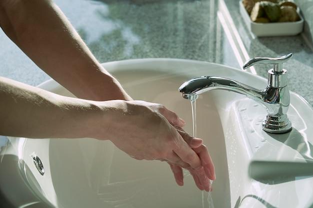 水で蛇口の下で手を洗う