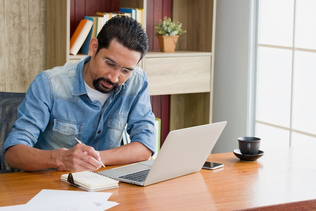 Владелец бизнеса или предприниматель использует ноутбук для работы и записи графиков работы в блокноте, сидя за столом в своем доме.