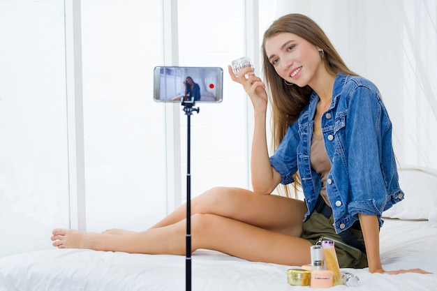 Женщина-блогер представляет косметику для красоты и транслирует прямую трансляцию в социальных сетях с технологией смартфона