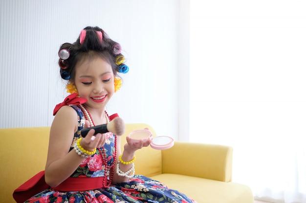 Маленькая девочка азиатка счастлива с косметикой