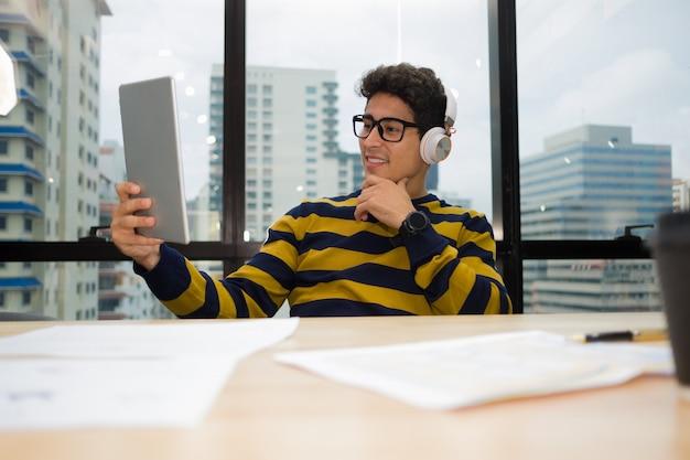 タブレットを押しながらヘッドフォンを着て机に座ってカジュアルなセーターの若いビジネス人々