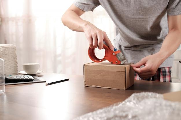 段ボール箱を梱包するスタートアップのビジネス所有者のクローズアップ。オンラインショッピングについて。