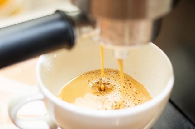 新鮮なコーヒードロップがコーヒーマシンからクローズアップ
