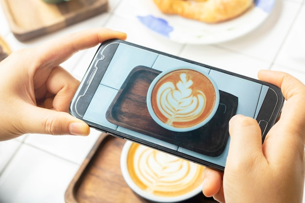 携帯電話で写真ラテコーヒーを飲む