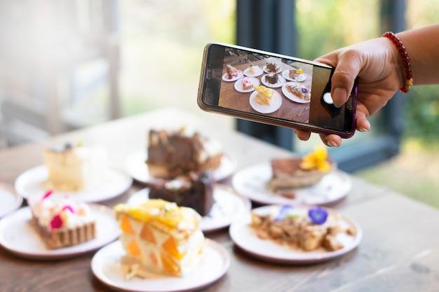 Девушки используют мобильный телефон, фотографируют еду и делятся в приложении рекламой онлайн бизнеса
