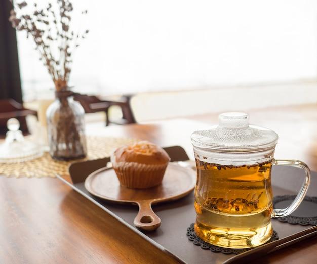 テーブルと白い光の背景にパンケーキとガラスのコップで熱いお茶