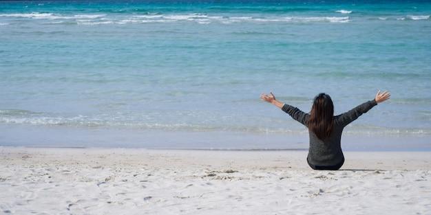 とても幸せな女砂の上に座って、美しい海の景色を眺めましょう。