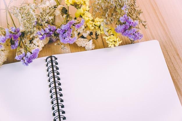 花の花と木のテーブルに白い空白のノートブック