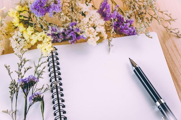 木製のテーブルの上に、花の花の束の近くの空白のノートブックにペンを置く