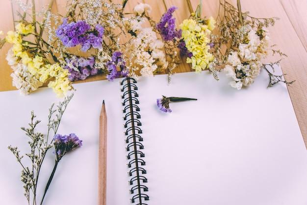 木製のテーブルの上の花の花の束の近くの空白のノートブックに鉛筆を置く