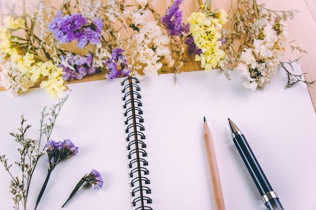 ペンと鉛筆、木製のテーブルの上の花の花の束の近くの空白のノートブックを置く