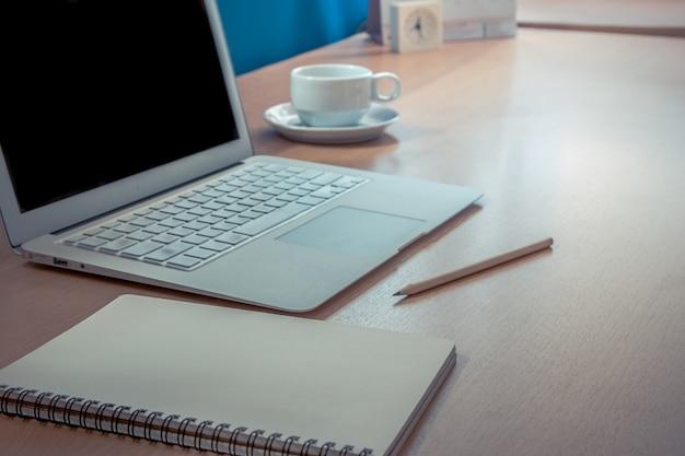 ノートパソコンと一杯のコーヒー、スマートフォンとペンの近くの木製のテーブルにノートを置きます。