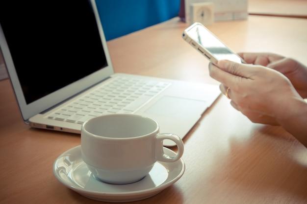 現代のデバイス、デジタルノートブックコンピューター、携帯電話を操作するビジネスマン。