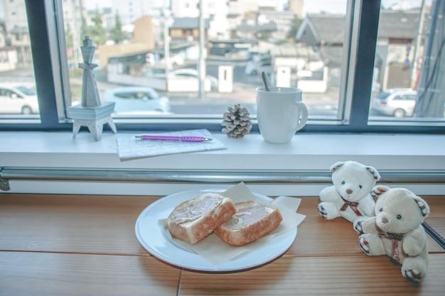 一杯のコーヒーとガラス窓の近くの木のバーにピーナッツバターのパン。旅行者は行く予定です。