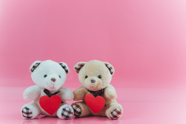 素敵なカップルのクマはピンクの背景と心を保持します。